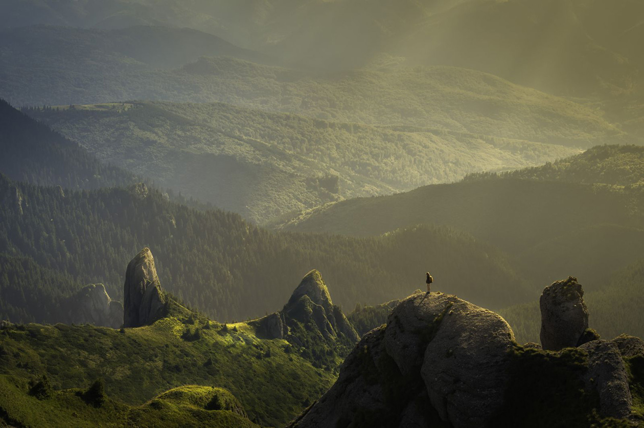 A girl stands on top of a hill in Romania