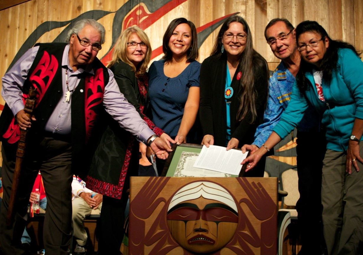 The Baha'i Community submission and gift being placed in the bentwood box by the three Commissioners, members of the Baha'i Community of Canada, and a member of the Survivors Committee. © Baha'i Community of Canada/Photo: Tobin Smith